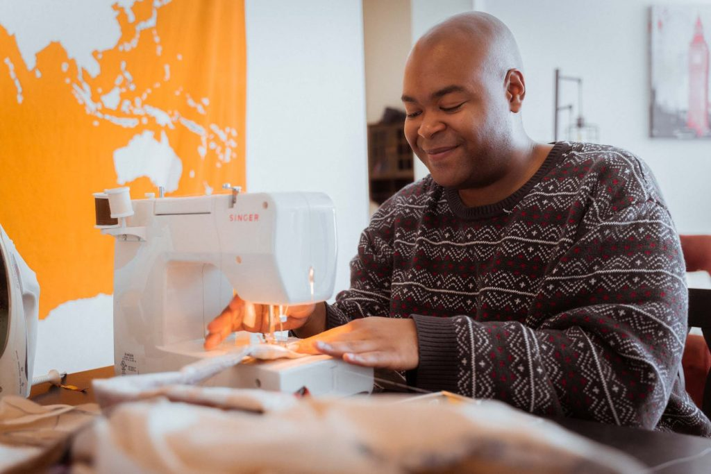 smiling black dressmaker working on sewing machine